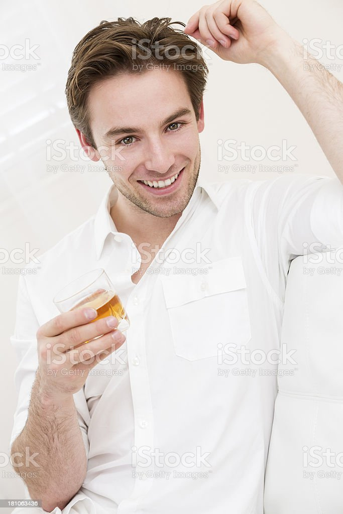 Young handsome man relaxing with a glass of whiskey royalty-free stock photo