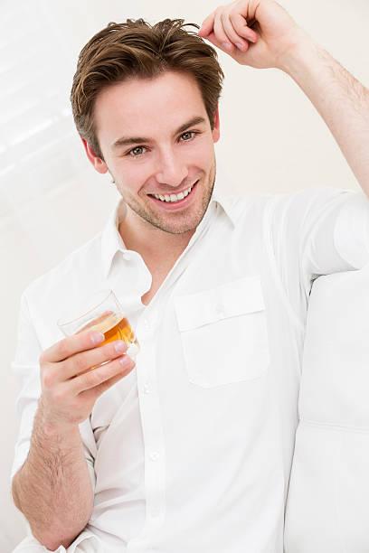 junger gut aussehender mann entspannend mit einem glas whisky - oliven wohnzimmer stock-fotos und bilder
