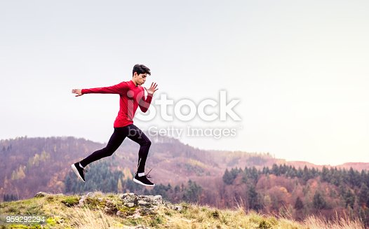 Young handsome man in red top running in nature.