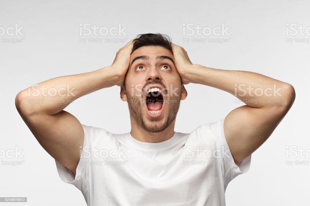 Hombre guapo joven gritara a vecinos ruidosos, por ruido, sosteniendo la cabeza con ambas manos, evitar lucha escucha - foto de stock