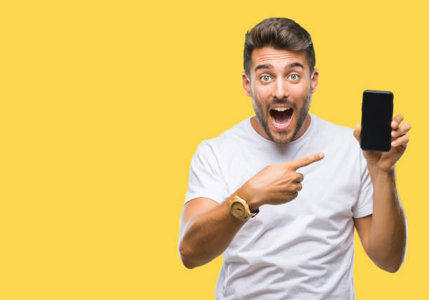 若いハンサムな男表示スマート フォン画面は孤立した背景の手と指で指している非常に満足して、 - 見せる ストックフォトと画像