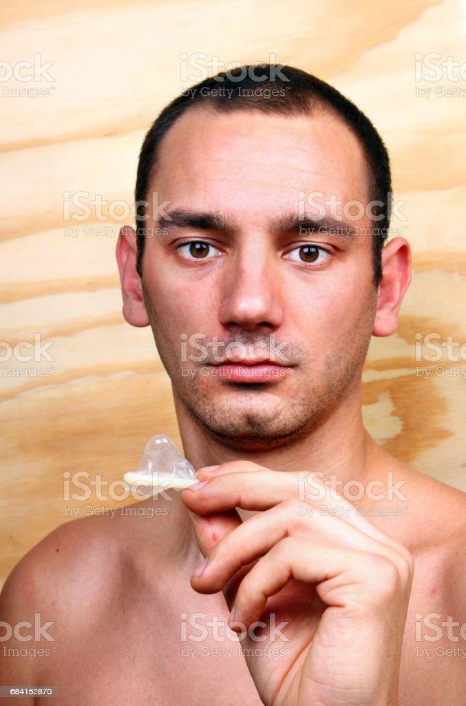 Young handsome man shows and keeps a condom royaltyfri bildbanksbilder