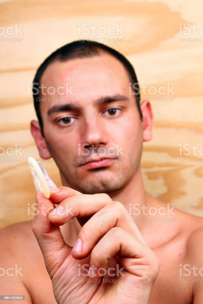 Young handsome man shows and keeps a condom foto stock royalty-free