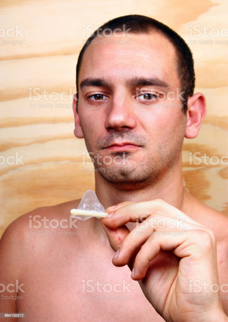 Young handsome man shows and keeps a condom zbiór zdjęć royalty-free