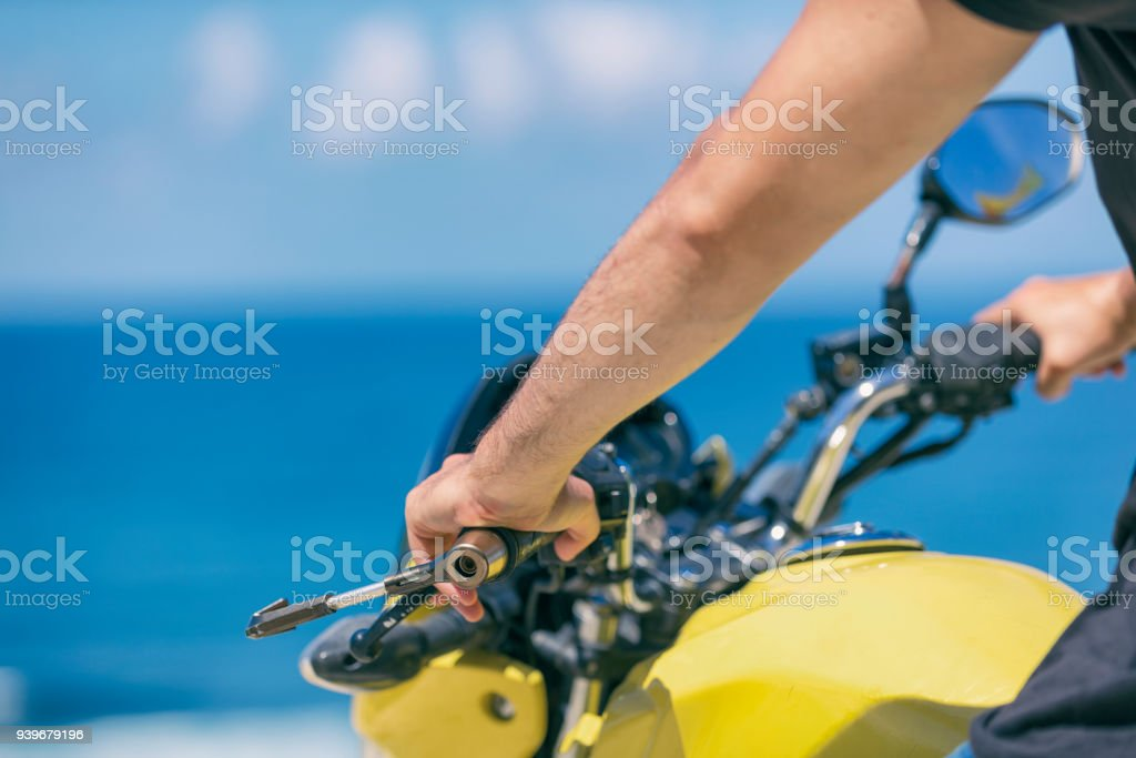 Young handsome man sitting on motorcycle on the tropical beach. Details. stock photo