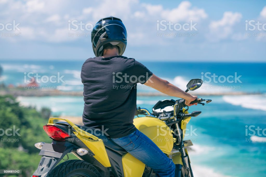 Young handsome man sitting on motorcycle on the tropical beach. stock photo