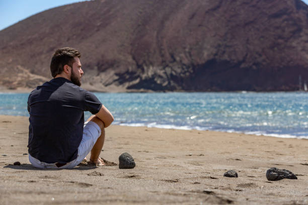 A young handsome man sitting on the sand in a beach while looking at the sea, in Tenerife, Canary Islands, Spain (closer view) stock photo