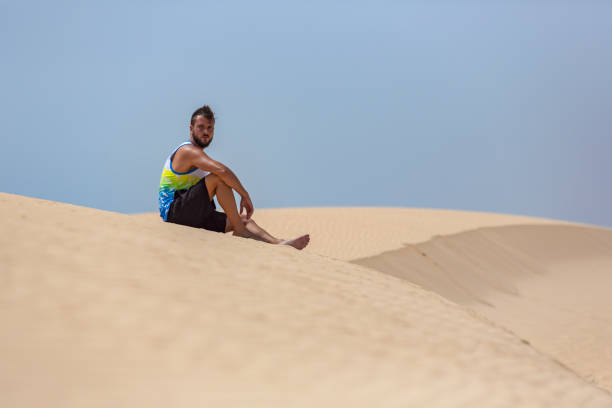 A young handsome man sitting on the sand of the dunes in a beach of Fuerteventura stock photo