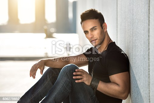 istock Young handsome man sitting wearing casual street style outfit 636275652