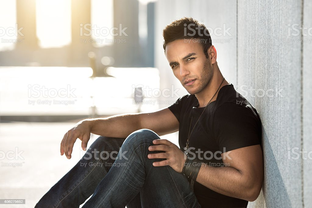 Young handsome man sitting wearing casual street style outfit stock photo