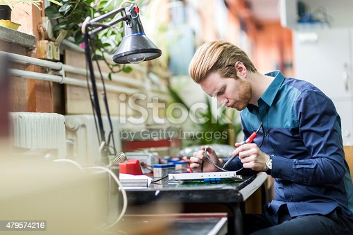 483784268 istock photo Young handsome man soldering a circuit board 479574216