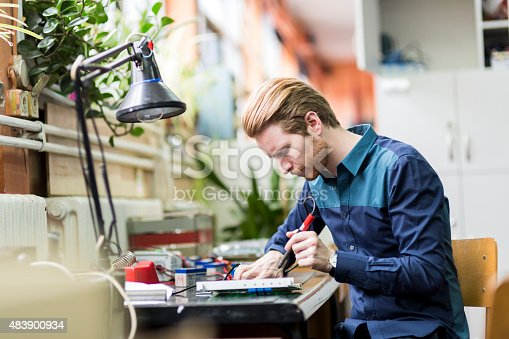 483784268 istock photo Young handsome man soldering a circuit board 483900934