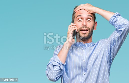 istock Young handsome man speaking on the phone over isolated background stressed with hand on head, shocked with shame and surprise face, angry and frustrated. Fear and upset for mistake. 1056716714