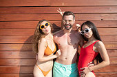 Having fun. Young handsome man standing and hugging two beautiful women in swimming suits