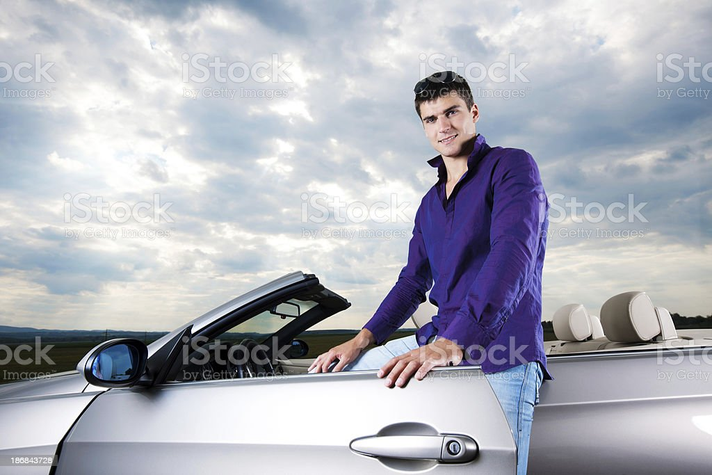 Young handsome man standing next to his cabriolet. stock photo