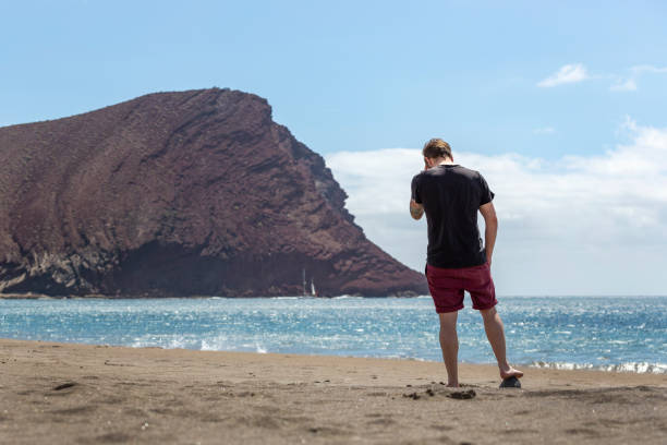 A young handsome man standing on the sand in a beach while touching his head, in Tenerife, Canary Islands, Spain stock photo