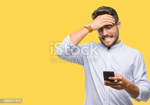 Young handsome man texting using smartphone over isolated background stressed with hand on head, shocked with shame and surprise face, angry and frustrated. Fear and upset for mistake.
