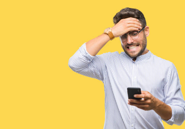 young handsome man texting using smartphone over isolated background stressed with hand on head, shocked with shame and surprise face, angry and frustrated. fear and upset for mistake. - discontented stock pictures, royalty-free photos & images