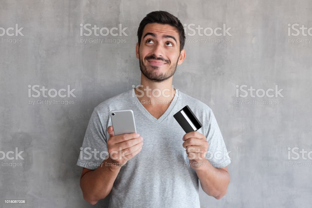 Young handsome man thinking about online shopping via internet, wearing gray t shirt, standing against textured wall, holding  credit card and cell phone stock photo