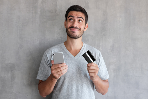 Young Handsome Man Thinking About Online Shopping Via Internet Wearing Gray T Shirt Standing Against Textured Wall Holding Credit Card And Cell Phone Stock Photo - Download Image Now