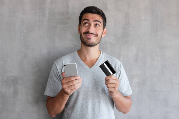 young handsome man thinking about online shopping via internet, wearing gray t shirt, standing against textured wall, holding  credit card and cell phone - credit card imagens e fotografias de stock
