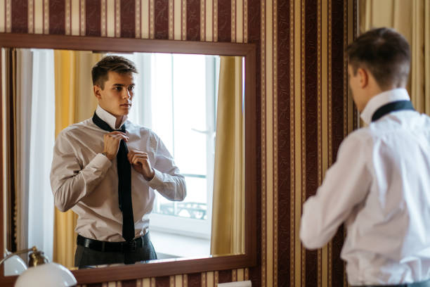 A young handsome man ties up a tie in front of a mirror stock photo