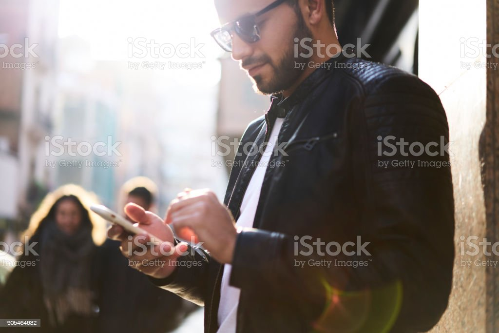 Young handsome man tourist using smartphone application to find right direction in urban setting, trendy hipster guy searching street number on mobile version of city map on his modern cellular - foto stock