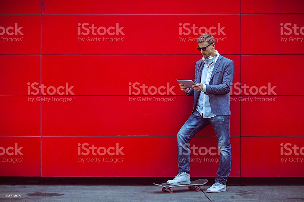 Young handsome man using digital tablet beside red wall. stock photo