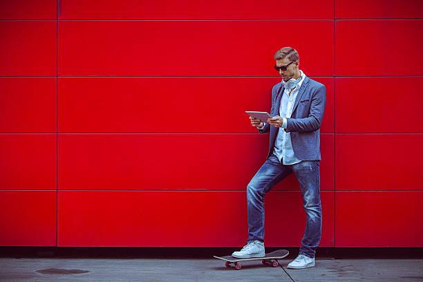 Jeune bel homme à l'aide de tablette numérique à côté de mur rouge. - Photo