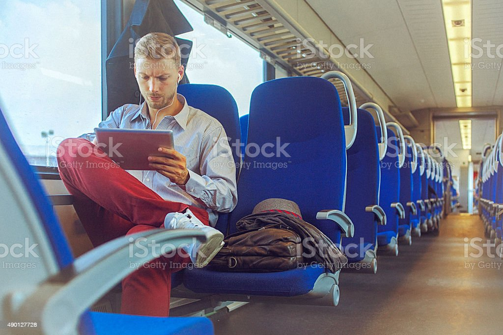 Young handsome man using digital tablet while commuting to work stock photo
