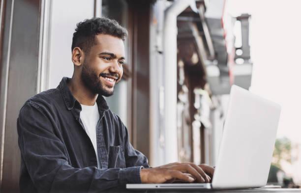 Junge stattliche Mann mit Laptop-Computer in einer Stadt – Foto
