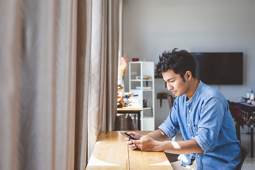 825083556 istock photo Young handsome man using smart phone at home, Man typing an sms message and working mobile devices, People lifestyle technology concept 1184787161