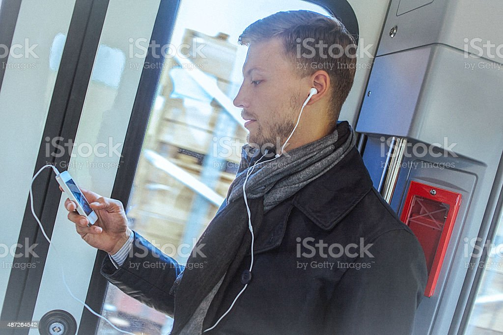 Young handsome man using smart phone while commuting to work stock photo