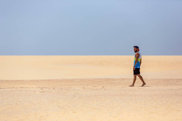 A young handsome man walking on the sand of the dunes in a beach of Fuerteventura stock photo