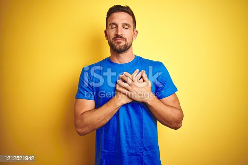1045886560 istock photo Young handsome man wearing casual blue t-shirt over yellow isolated background smiling with hands on chest with closed eyes and grateful gesture on face. Health concept. 1212521942