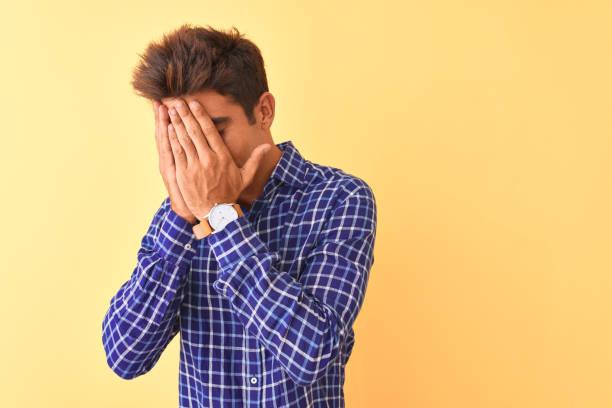 joven hombre guapo con camisa casual de pie sobre fondo amarillo aislado con expresión triste cubriendo la cara con las manos mientras llora. concepto de depresión. - vergüenza fotografías e imágenes de stock