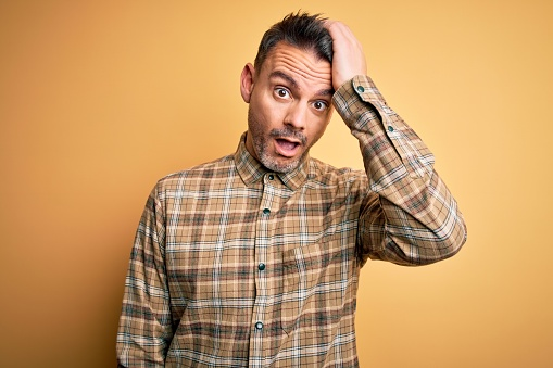 1046559700 istock photo Young handsome man wearing casual shirt standing over isolated yellow background surprised with hand on head for mistake, remember error. Forgot, bad memory concept. 1214275656