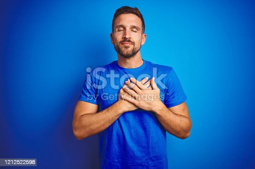 1045886560 istock photo Young handsome man wearing casual t-shirt over blue isolated background smiling with hands on chest with closed eyes and grateful gesture on face. Health concept. 1212522598