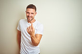Young handsome man wearing casual white t-shirt over isolated background Beckoning come here gesture with hand inviting welcoming happy and smiling