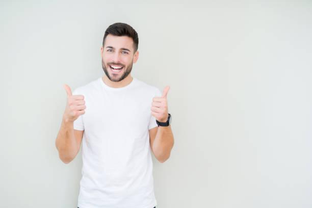 若いハンサムな男は、手で肯定的なジェスチャーをやって孤立した背景の成功サイン上のカジュアルホワイト t シャツを着て、笑顔と幸せに親指。陽気な表情でカメラを見て、勝者のジェス� - 親指 ストックフォトと画像
