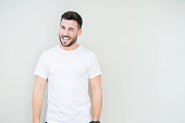 istock Young handsome man wearing casual white t-shirt over isolated background winking looking at the camera with sexy expression, cheerful and happy face. 1097762014