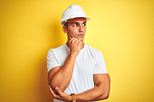 Young handsome man wearing construction helmet over yellow isolated background with hand on chin thinking about question, pensive expression. Smiling with thoughtful face. Doubt concept.
