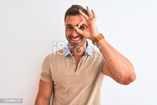 1045886560 istock photo Young handsome man wearing elegant t-shirt over isolated background doing ok gesture with hand smiling, eye looking through fingers with happy face. 1204994707
