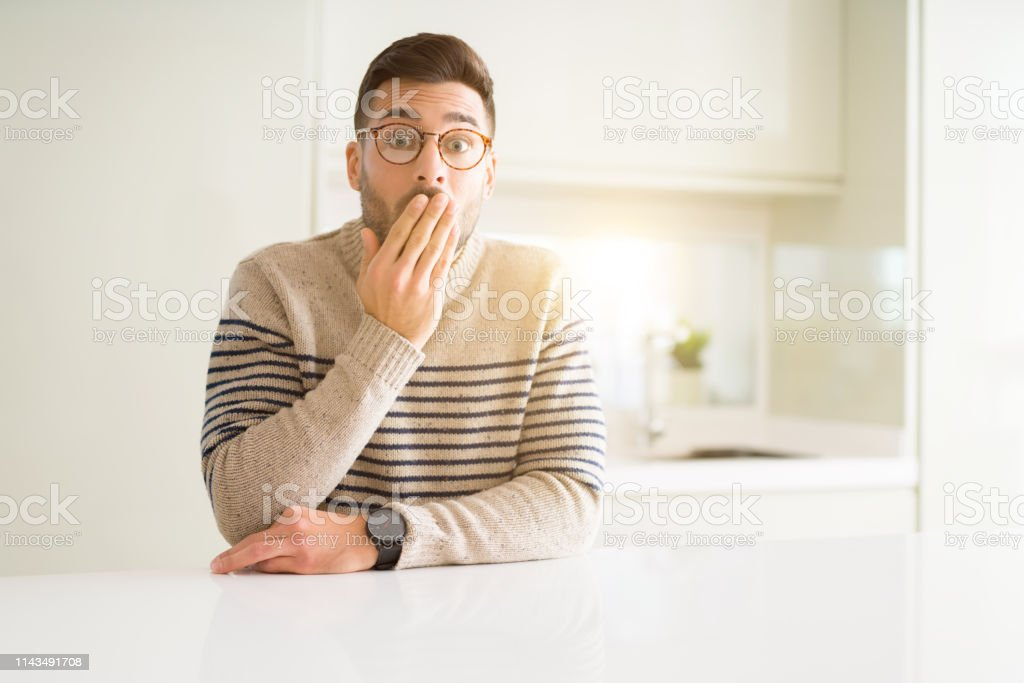 Young handsome man wearing glasses at home cover mouth with hand...