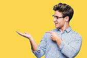 istock Young handsome man wearing glasses over isolated background amazed and smiling to the camera while presenting with hand and pointing with finger. 1124797242