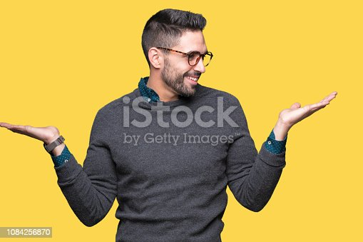 istock Young handsome man wearing glasses over isolated background Smiling showing both hands open palms, presenting and advertising comparison and balance 1084256870