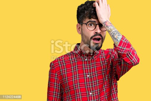 1046559700istockphoto Young handsome man wearing glasses over isolated background surprised with hand on head for mistake, remember error. Forgot, bad memory concept. 1124224458