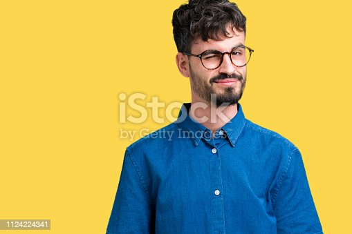 istock Young handsome man wearing glasses over isolated background winking looking at the camera, cheerful and happy face. 1124224341