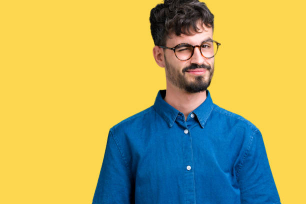 young handsome man wearing glasses over isolated background winking looking at the camera, cheerful and happy face. - blinking stock pictures, royalty-free photos & images