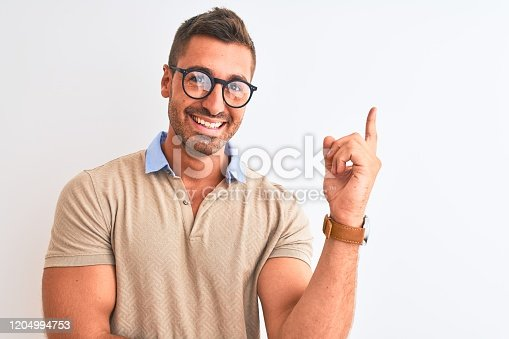 1045886560 istock photo Young handsome man wearing glasses over isolated background with a big smile on face, pointing with hand and finger to the side looking at the camera. 1204994753